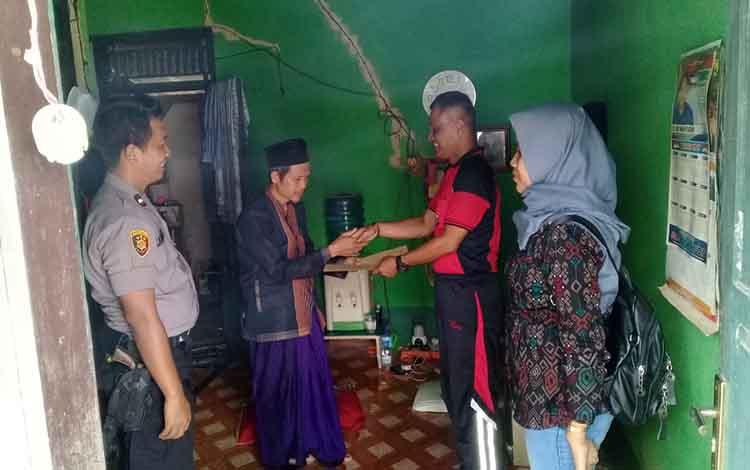 Anggota Polsek Pangkalan Banteng kmenyerahkan bantuan dan diterima oleh Ustad Japar pengasuh Panti Asuhan Ishiahul Iman Desa Amin Jaya, Jumat, 13 Desember 2019.