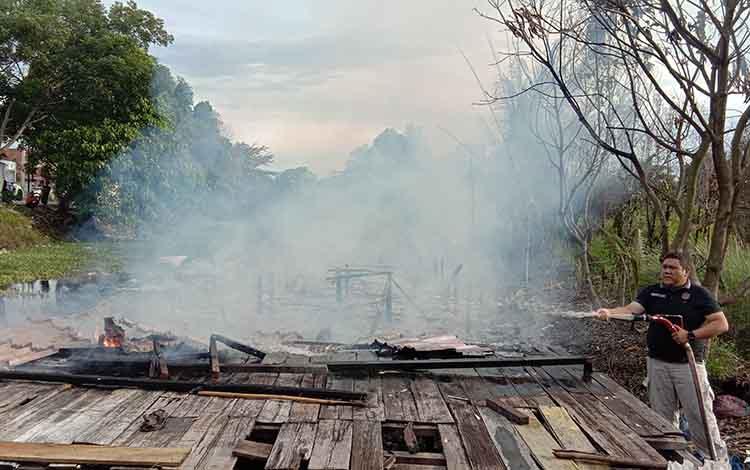 Salah satu petugas ERP saat melakukan pemadaman rumah milik S yang hangus terbakar, Jumat 13 Desember 2019.