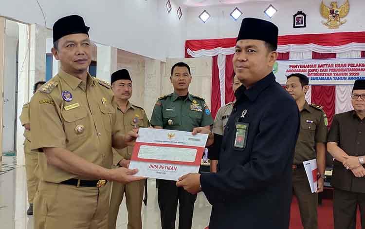 Bupati Sukamara, Windu Subagio saat menyerahkan DIPA kepada Kepala Pengadilan Agama (PA) Sukamara, M Arqom Pamulutan.