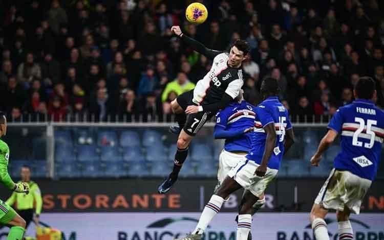 Penyerang Juventus Cristiano Ronaldo (tengah) menanduk bola untuk menjadi gol penentu kemenangan dalam pertandingan Liga Italia melawan Sampdoria yang dimainkan di Stadion Luigi Feraris, Genoa, Rabu (18/12/2019). (ANTARA/AFP/MARCO BERTORELLO)