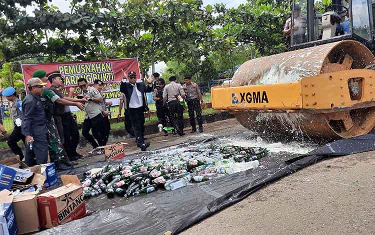 Puluhan botol minuman keras dimusnahkan dengan cara digiling menggunakan alat berat.