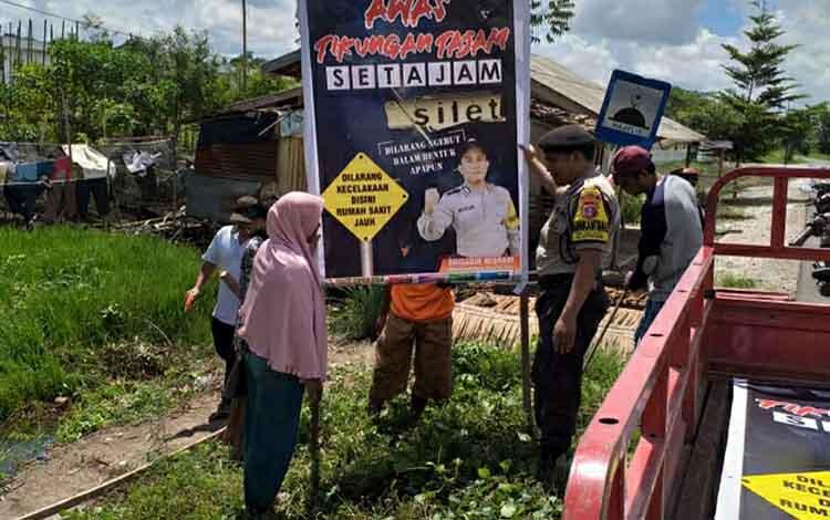 Anggota Polsek Kapuas Barat saat memasang spanduk imbauan pada titik rawan kecelakaan lalu lintas di kawasan Jalan Lintas Mandomai.
