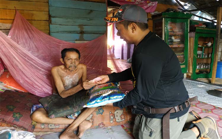 Ketua Seruyan Bike Club, Reson Rusdianto menyerahkan bantuan beras dan uang kepada warga kurang mampu