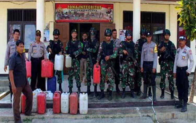 Satgas Pamtas RI-PNG Batalyon Infanteri Mekanis Raider 411 Pandawa Kostrad Pos Kuler dan Polsek Onggaya memperlihatkan barang bukti Miras lokal jenis Sopi