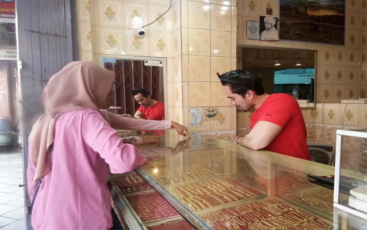 Marjuki pemilik toko emas di PPM Sampit melayani pembeli. Sementara itu menjelang Natal, penjualan emas meningkat 30 persen