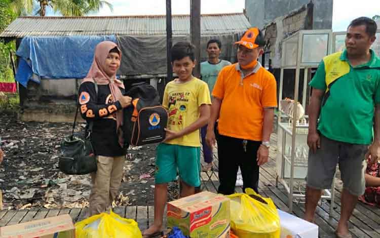 Petugas BPBD Kapuas menyalurkan bantuan kepada korban terdampak kebakaran rumah di Desa Tamban Luar, Kecamatan Bataguh
