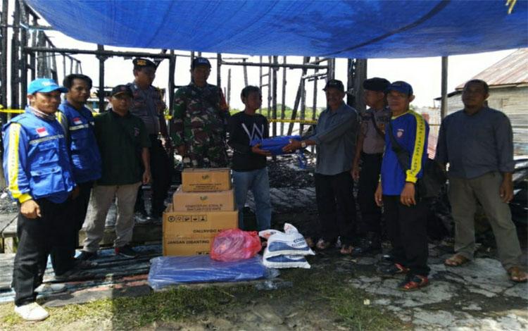 Petugas Dinas Sosial Kapuas bersama Tagana menyerahkan bantuan kepada korban kebakaran rumah di Desa Saka Lagun RT 04, Kecamatan Pulau Petak