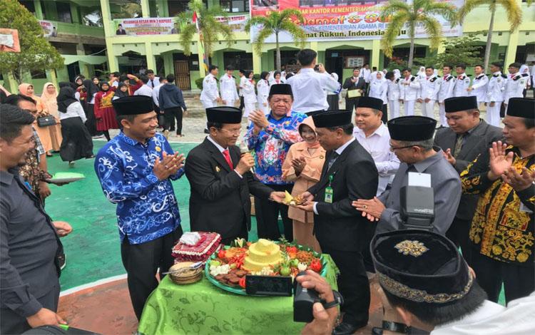 Kepala Kemenag Kapuas Ahmad Bahruni menerima potongan nasi tumpeng dari Wabup Kapuas HM Nafiah Ibnor. Hari Amal Bhakti momentum tingkatkan sinergi dengan pemerintah daerah