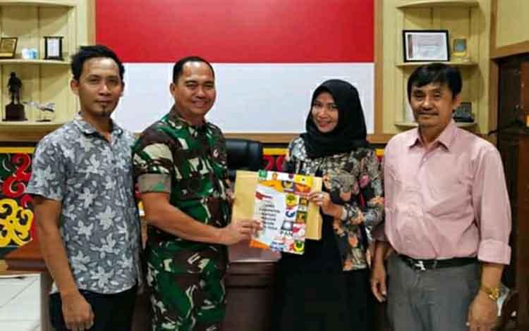 Ketua KPU Kapuas Jamilah Maisura menyerahkan buku profil Anggota DPRD kepada Dandim 1011 Letkol Kav Bambang Kristianto Bawono, Selasa sore, 7 Januari 2020.
