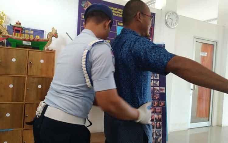 Petugas Pengamanan Pintu Utama (P2U) Lembaga Pemasyarakatan Kelas III Sukamara saat memeriksa pengunjung.