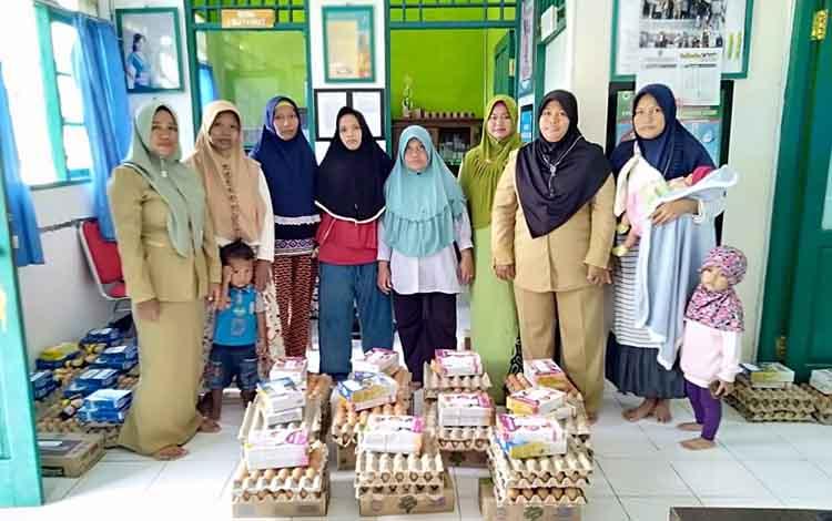 Petugas kesehatan Desa Bangun Harja saat menyerahkan bantuan untuk penanganan stunting dan ibu hamil dj¡desa setempat