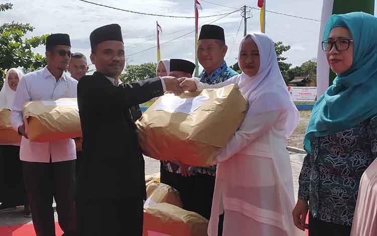 Kepala Kemenag Sukamara, Nur Widiyantoro menyerahkan hadiah usai upacara Hari Amal Bhakti Kemenag, beberapa waktu lalu.