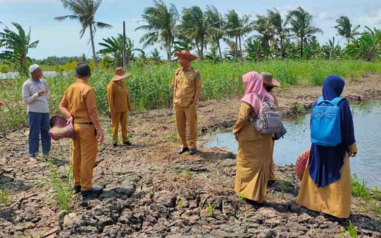 Bupati Sukamara, Windu Subagio bersama Kepala Dinas Perikanan (Diskan) Sukamara, Fandedi saat memantau kolam pembudidahaan kakap putih Desa Sungai Pasir.