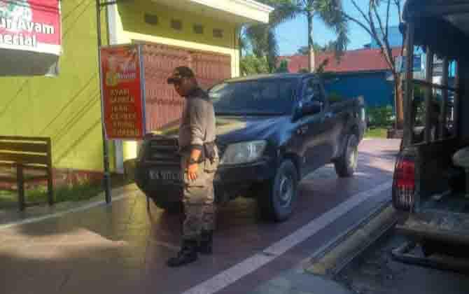 Personel Satpol PP beri teguran ke kendaraan yang parkir di trotoar.