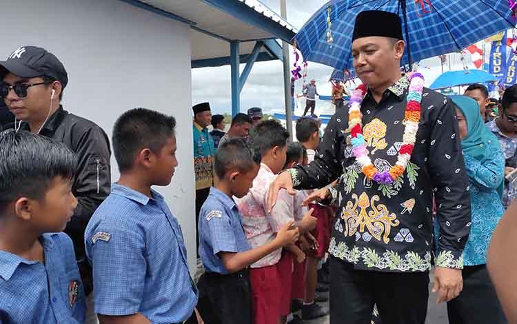 Bupati Sukamara, Windu Subagio menyalami pelajar yang menyambut di Kecamatan Jelai.