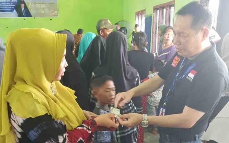 Kepala Dinas Dukcapil Kobar, M Gusti Imansyah menyerahkan KIA kepada warga Desa Kubu, Kecamatna Kumai, Minggu, 26 Januari 2020.