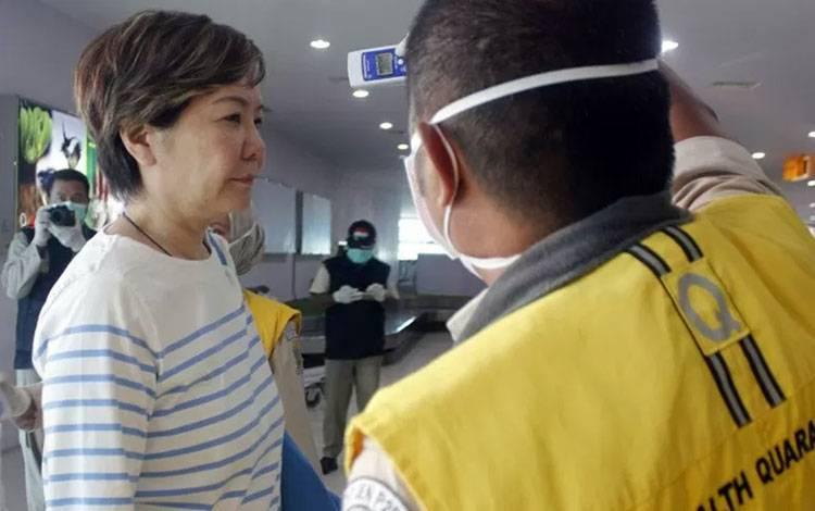 Petugas Karantina Kesehatan memeriksa suhu tubuh wisatawan asal China (kiri) yang baru mendarat di bandara DEO Kota Sorong, Papua Barat, Ahad (26/1/2020). Otoritas Bandara dan Karantina kesehatan melakukan antisipasi penyebaran virus Corona (nCoV) terhadap Warga Negara Asing (WNA) asal Cina dengan mennyiapkan alat pendeteksi suhu badan. ANTARA FOTO/Olha Mulalinda/nz