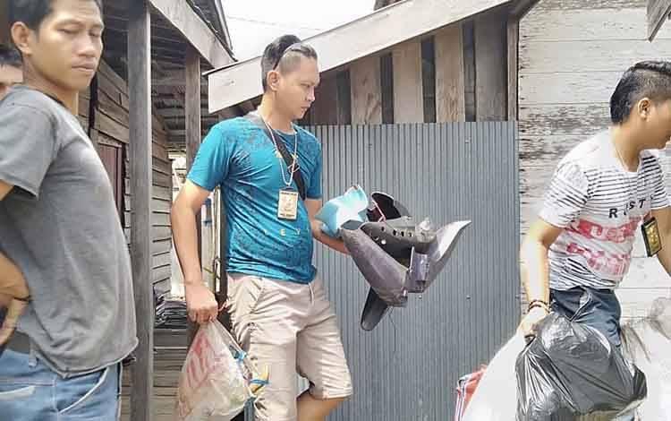 Anggota berpakain preman mengamankan barang bukti dari rumah pelaku