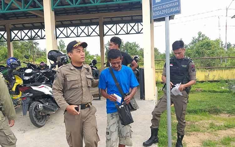 Anggota Satpol PP mengamankan pengunjung yang merokok di kawasan RSUD Lamandau, Selasa, 28 Januari 2020.