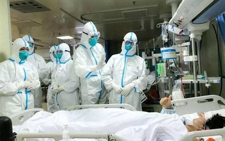 Seorang pasien 2019-nCoV di Rumah Sakit Hankou, Wuhan, memberikan isyarat jempol kepada tim kesehatan dari Second Military Medical University, Senin (27/1/2020). (ANTARA/HO-ChinaNews/mii)