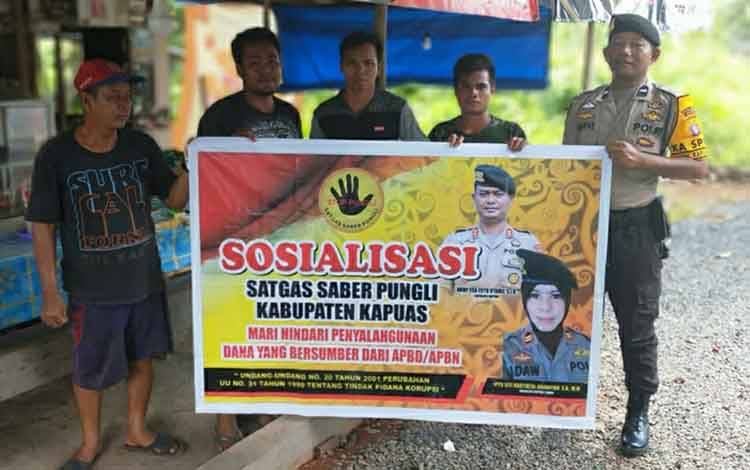 Anggota Polsek Kapuas Timur saat mensosialisasikan Satgas Saber Pungli kepada warga di Desa Anjir Mambulau Timur KM 7.