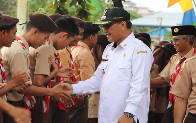 Wakil Bupati Katingan, Sunardi Litang menyalami anggota pramuka saat pelantikan pengurus Kwaran Kecamatan Mendawai, Rabu, 29 Januari 2020.