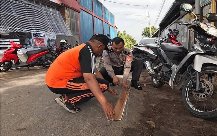 Anggota Satlantas Polres Kobar melakukan gotong-royongdengan melakukan pengecatan marka jalan untuk membuat Kampung Percontohan Tertib Lalu Lintas.