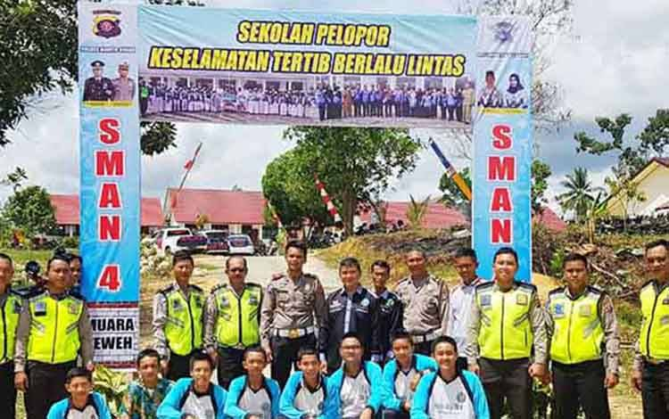 Personel Satlantas Polres Barito Utara bersama-sama siswa SMAN 4 Muara Teweh saat membangun gapura.