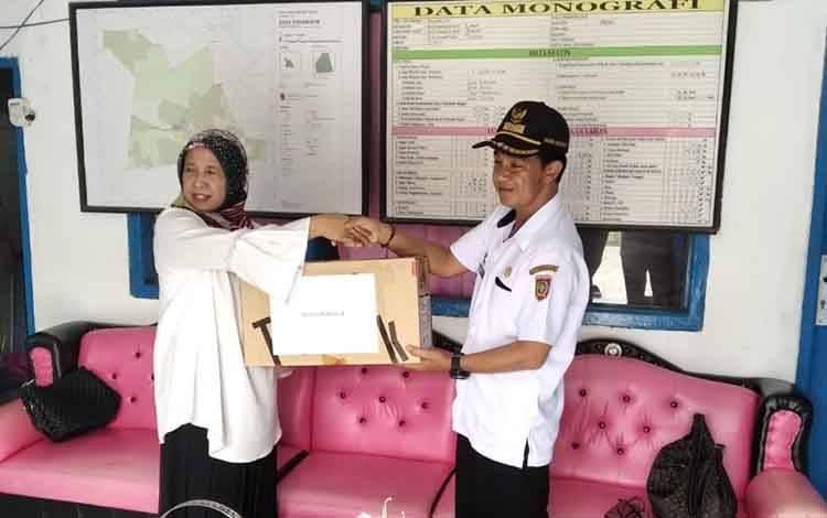Kepala Dinas Perpustakaan dan Kearsipan Kobar, Zainah menyerahkan bantuan 50 buku dan 2 komputer kepada Kepala Desa Sakabulin, Edi Marthono