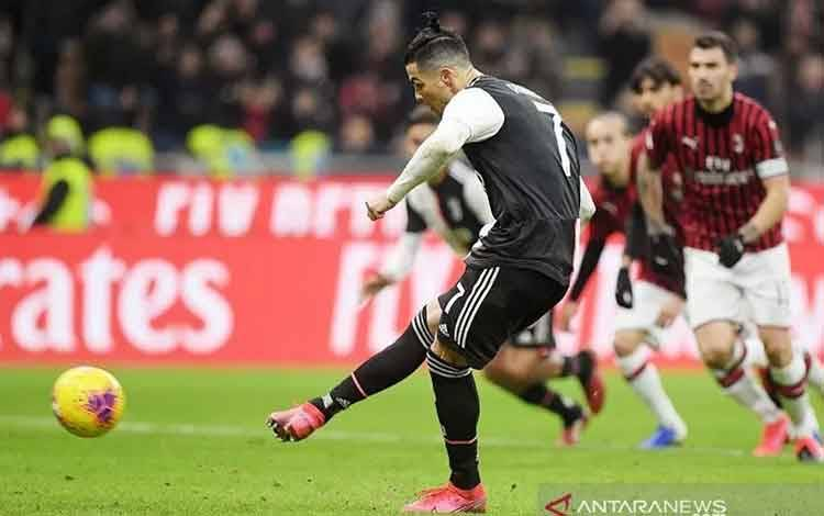Megabintang Juventus Cristiano Ronaldo mengeksekusi tendangan penalti untuk mencetak gol ke gawang AC Milan dalam laga pertama semifinal Coppa Italia di Stadion San Siro, Milan, Italia, Kamis (13/2/2020) waktu setempat. (ANTARA/REUTERS/Alberto Lingria)