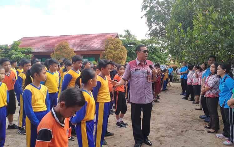 Kepala Disdikpora Kabupaten Gunung Mas Agung ketika memberikan arahan kepada para murid di halaman SDN 3