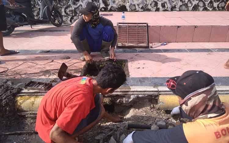 Petugas Dinas PUPR Kotawaringin Barat memerbaiki drainase yang tersumbat di Pangkalan Bun.
