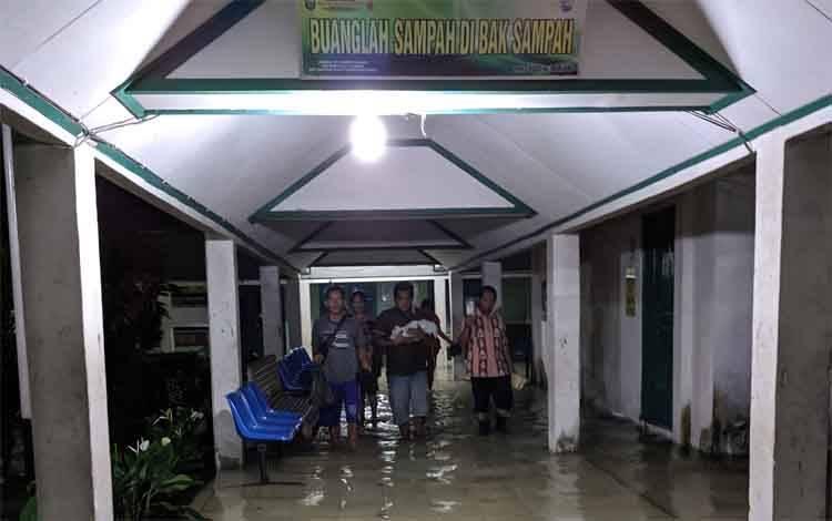 Sejumlah keluarga pasien saat melintas di lorong menuju kamar pasien RSUD dr Murjani Sampit yang banjir, Minggu, 16 Februari 2020
