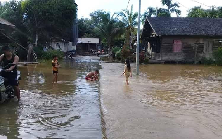 Sejumlah anak-anak dan warga Desa Tumbang Koling yang dilanda banjir, saat bermain air, Senin, 17 Februari 2020.