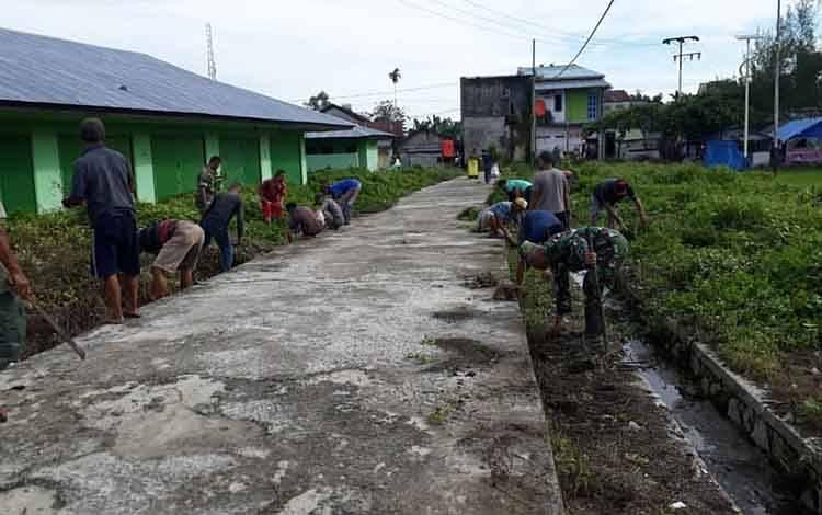 Anggota TNI Koramil 1014-06/Sukamara melakukan pembersihan parit untuk mengantisipasi banjir dan wabah penyakit DBD.