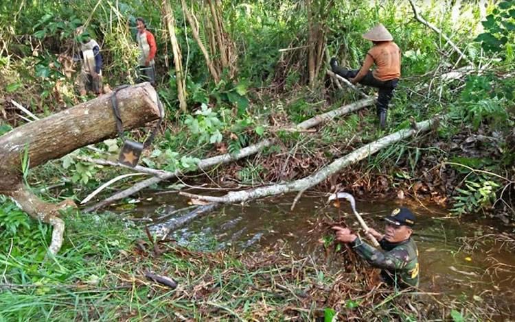 Anggota Koramil Kapuas Murung ikut gotong royong bersihkan saluran parit di Desa Palingkau Sejahtera