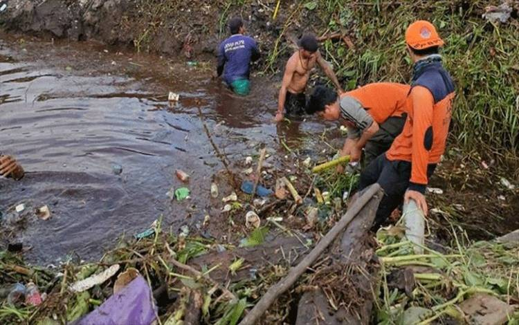 Sejumlah anggota BPBD Palangka Raya membersihkan tumpukan sampah di drainase.