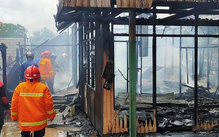 Sejumlah petugas pemadam kebakaran saat berupaya menjinakan api yang membakar rumah, Rabu, 19 Februari 2020.