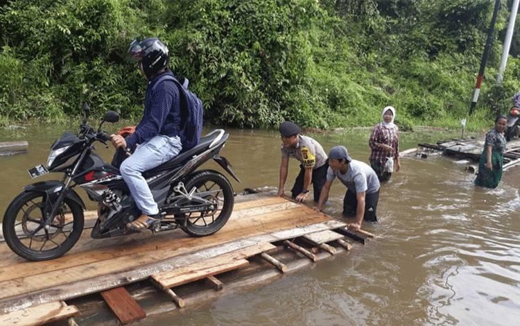 Bhabinkamtibmas Juking Pajang membantu warga menyeberang dengan rakit agar dapat melewati banjir yang memutus akses jalan desa menuju Ibukota Puruk Cahu, Jumat, 21 Februari 2020.