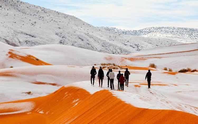 Wisatawan melihat salju yang menutupi sebagian Gurun Sahara di Kota Ain Sefra di Aljazair. Salju menutupi bukit pasir merah ini merupakan kejadian yang sudah ketiga kalinya dalam 37 tahun
