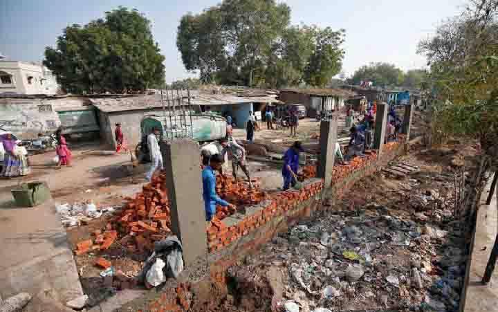 Pekerja konstruksi membangun tembok di sepanjang daerah kumuh sebagai bagian dari upaya mempercantik rute yang akan ditempuh Presiden Donald Trump dan Perdana Menteri India Narendra Modi selama kunjungan Trump ke Ahmedabad, India, 13 Februari 2020. (foto : REUTERS via teras.id)