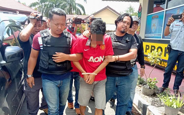 Pelaku pemerkosaan terhadap pelajar SMP, MA (26) yang berprofesi sebagai guru honorer di salah satu sekolah di Kecamatan Sebangau Kuala, Kabupaten Pulang Pisau saat digiring oleh anggota Polres Pulang Pisau, Minggu, 23 Febuari 2020.