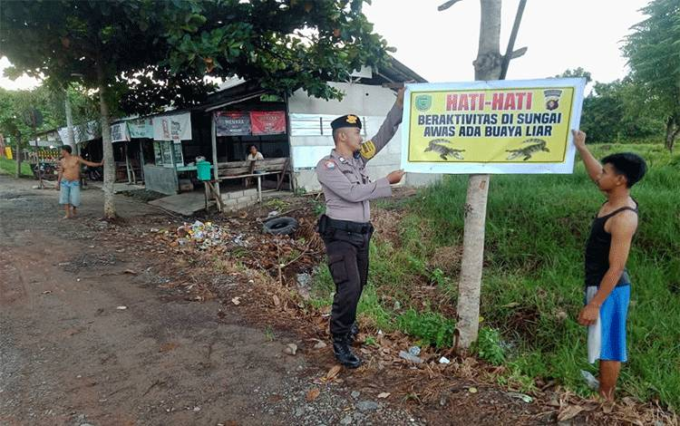 Anggota Polsek Kahayan Hilir memasang imbauan terkait kemunculan buaya di Desa Mantaren, Kecamatan Kahayan Hilir, Kabupaten Pulang Pisau, Selasa, 25 Febuari 2020.