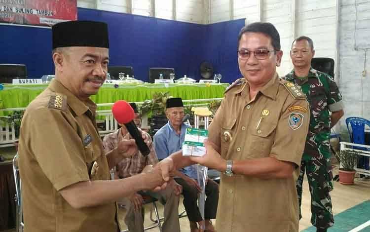 Bupati Seruyan Yulhaidir saat menyerahkan BPJS Kesehatan kepada camat Seruyan Hulu untuk dibagikan kepada warganya.