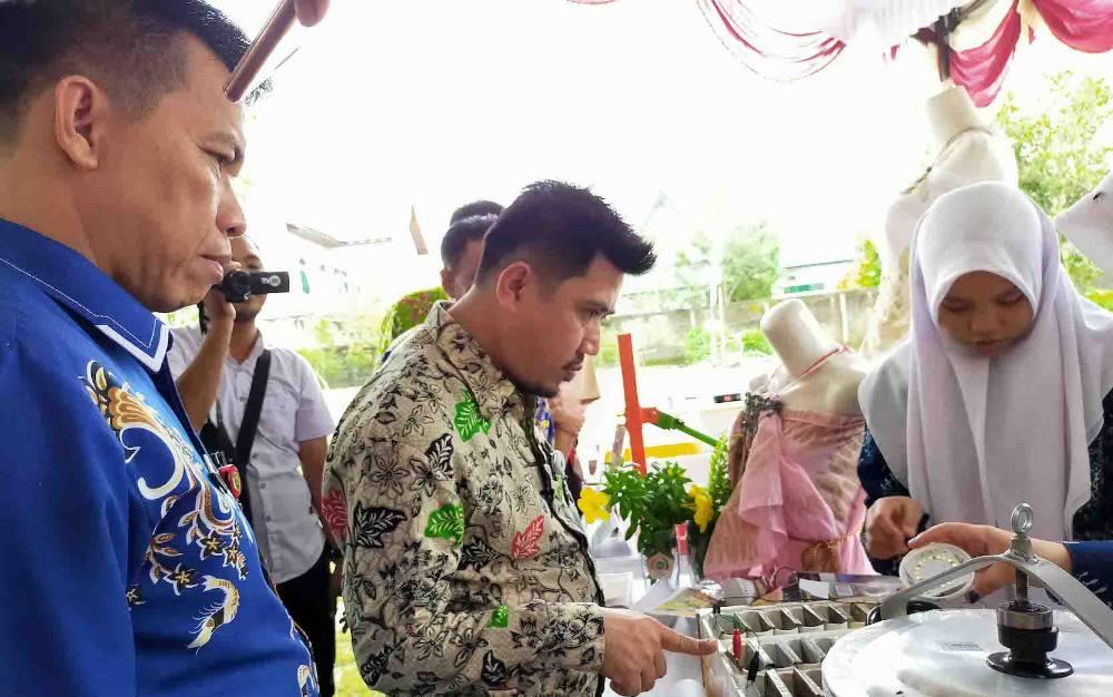 Kepala Dinas PMDes Kotim, Hawianan (batik biru) menyaksikan karya peserta lomba inovasi teknologi tepat guna, Kamis, 27 Februari 2020.