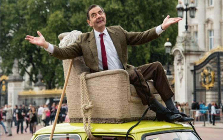 """Komedian """"Mr. Bean,"""" berpose di atas atap mobil Mini Cooper di sekitar Istana Buckingham, London, 4 September 2015. Acara ini diselenggarakan untuk merayakan 25 tahun karakter Mr. Bean. Jonathan Short/Invision/AP"""