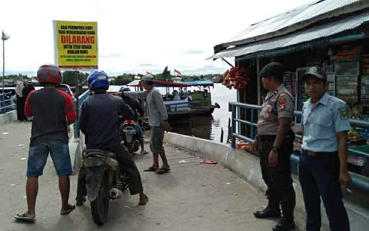 Personel Polsek Kapuas Barat saat melakukan pengamanan dan memberikan imbauan di Feri Penyeberangan Saka Mangkahai pada Sabtu, 29 Februari 2020.