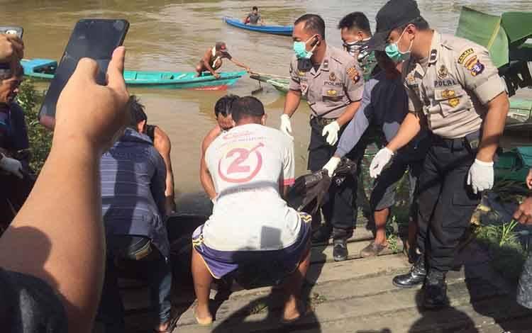 Petugas dan warga saat mengevakuasi sosok mayat korban tenggelam di Mentaya Hulu, Senin, 2 Maret 2020.