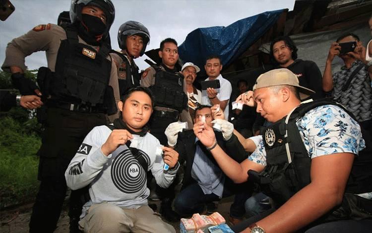 Petugas kepolisian memperlihatkan sejumlah barang bukti sabu dan uang tunai hasil penggeledahan di rumah Saleh wilayah Puntun, Kamis 5 Maret 2020.