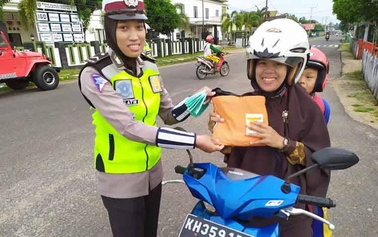 Personel Satlantas Polres Seruyan menyerahkan jas hujan kepada pengendara yang tertib.